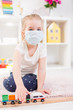 Little blonde girl in a medical mask playing with toy train on a floor in a light room at hone during quarantine.