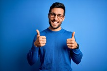 Young Handsome Man With Beard Wearing Casual Sweater And Glasses Over Blue Background Success Sign Doing Positive Gesture With Hand, Thumbs Up Smiling And Happy. Cheerful Expression And Winner