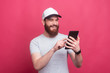Leinwandbild Motiv Portrait of cheerful man with beard smiling and using his tablet over pink background