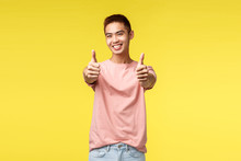 Lifestyle, Travel And People Concept. Satisfied Cute Asian Male Student Recommend Best Language Courses In Town, Show Guarantee Or Approval Sign, Thumb-up Smiling Pleased, Yellow Background