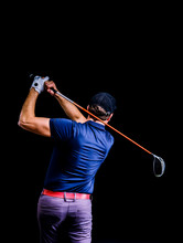 Close-up Of A Golf Player Intent On Perfecting The Swing Isolated On Dark Background. Vertical Image