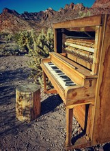 Old Piano With Mountains In Background