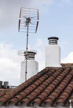 White Painted Village Chimneys With Lime Television Antennas And Red Clay Tile Roofs