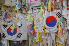 Barbed Wire Fence Separates South From North Korea - South Korean Flags And Prayer Wishes Attached To Fence For Those Separated Or Who Had Died During The Korean War - NOVEMBER 2013