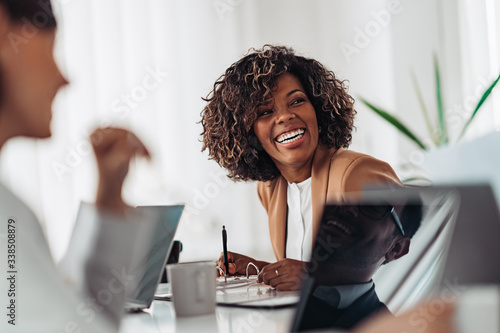 Obraz Portrait of cheerful businesswoman smiling at the meeting - fototapety do salonu