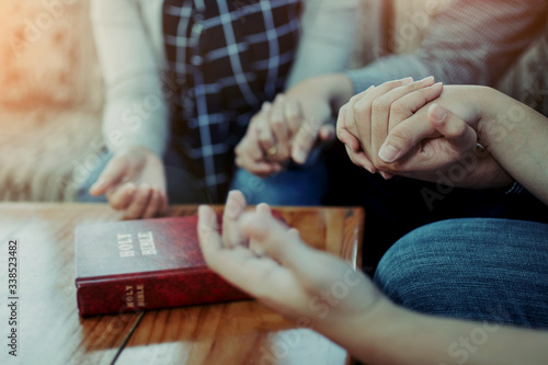 Canvas-taulu Close up of  people group holding hand and pray together over a blurred holy bib