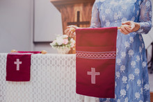 Close Up Of A Woman Hand Holding Red Offering Bag In Church, Focus On The White Cross In Offering Bog