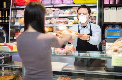 Fototapeta Shopkeeper serving a customer while wearing a mask obraz