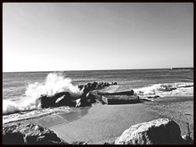 Waves Breaking On Rocks Against Clear Sky