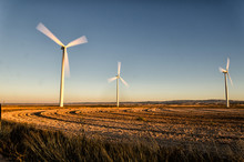 Three Wind Turbines On Landscape Against Clear Sky