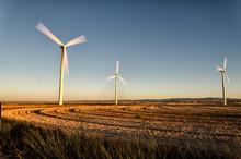 Three Wind Turbines On Landsca...