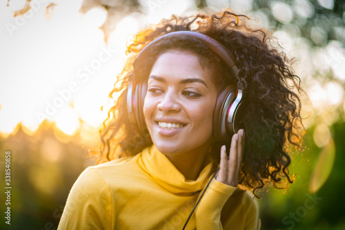 Obraz na plátně Close-up of african american woman listening to music with headphones outdoors