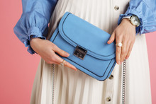 Women`s Fashion Concept: Model Holding Trendy Small Blue Faux Leather Bag, Wearing Stylish Wrist Watch, Beautiful Rings
