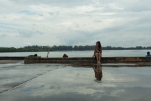 Backpacking Woman Traveling In Thailand, Reflection On The Ground While Waiting For The Taxi Boat After Rainnig
