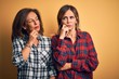 Middle age beautiful couple of sisters wearing casual shirt over isolated yellow background with hand on chin thinking about question, pensive expression. Smiling with thoughtful face. Doubt concept.