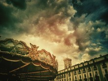 Swing Carousel And Building Against Dramatic Sky