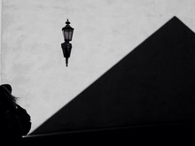 Lamp With Some  Shadowy  Pyramidal Structure And A Woman.