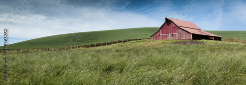 Photographie a panorama of green fields and a fence leading to an old red barn