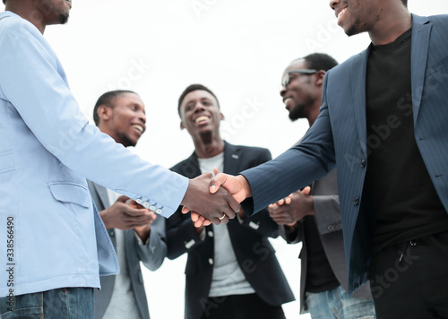 young business partners shaking hands to applause of employees Canvas Print