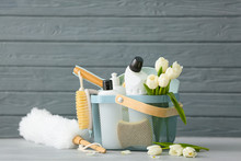 Set Of Cleaning Supplies And Spring Flowers On Grey Wooden Background