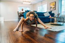 Smiling Girl Doing Crab Crawl On Living Room Floor