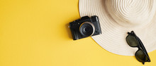 Flat Lay Summer Female Fashion Straw Hat, Sunglasses, Vintage Camera On Yellow Background. Top View Stylish Traveler Accessories. Summer Holiday Vacation, Travel, Tourism Concept