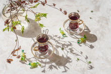 Young Tender Branches Of Colorful Color, Shadows On The Table, Cups With Fruit Tea, Openwork Background. Spring Sunny Morning