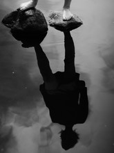 Reflection Of Person In Puddle Standing On Rocks