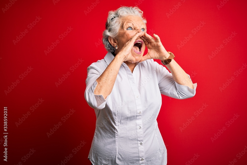 Fototapeta Senior beautiful woman wearing elegant shirt standing over isolated red background Shouting angry out loud with hands over mouth