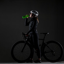 Girl Posing On Roadbike. Drinking From Green Cycling Water Bottle. White Protective Helmet. Side Lit Cyclist Against Dark Background.