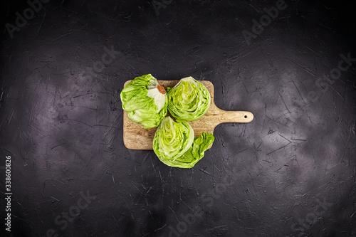 Fototapeta Iceberg lettuce (crisphead lettuce) on wooden cutting board on black stone table background, top view obraz