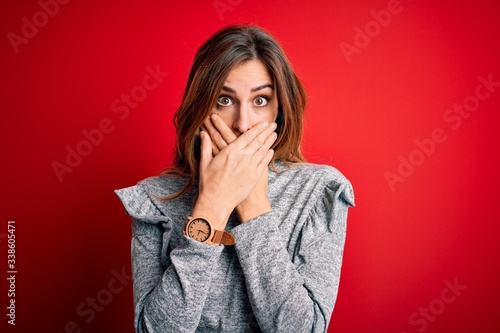 Young beautiful brunette woman wearing casual sweater standing over red background shocked covering mouth with hands for mistake Canvas Print