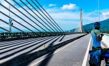 Cyclist Standing On A Bridge