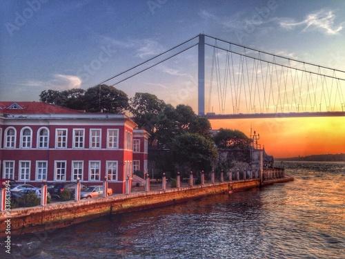 Fotografie, Obraz Bosphorus Bridge And Buildings Against Sky At Sunset
