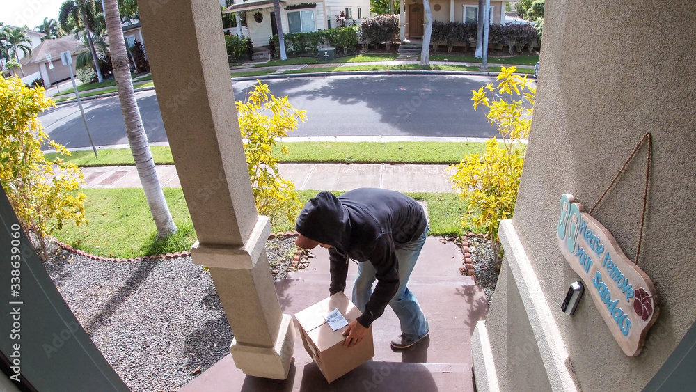 Fototapeta Person stealing delivery package from porch steps, surveillance camera view