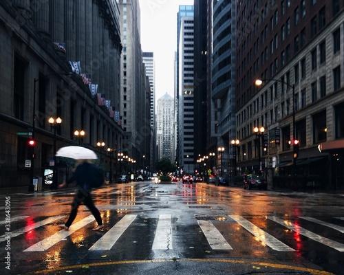 Vászonkép Man Crossing City Street During Rain