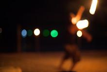 Defocused Image Of Man Performing Fire Stunt On Beach At Night