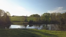 Aerial Approach To A Pond In A Green Meadow And Rolling Hills In The Idyllic Setting - Sky Reflecting Off The Surface Of The Still Water