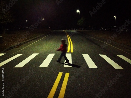 Fotografiet Child Crossing Road At Night