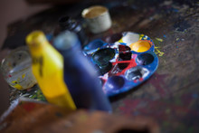 Palette And Paint Can On Workbench In Workshop