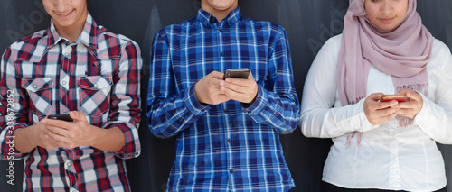 Photo arab teenagers group using smart phones for social media networking