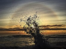 Water Splashing In Sea Against Sky At Sunrise