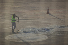 Disaser! A Broken Glass Window On The Apron Of The Modern Airport. Airport Ground Crew Member Trying To Clean Up Glass Debris On The Apron.