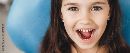 Happy caucasian girl with opened mouth smiling at camera after a teeth examinati Fototapeta