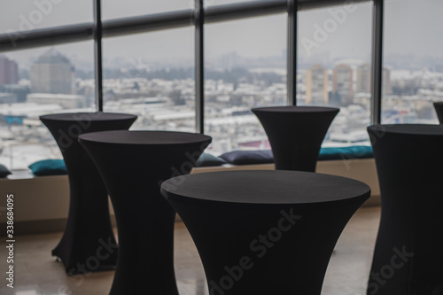 Multitude of empty elegant black standing tables for lunch reception with a nice view behind over the city blocks Canvas Print