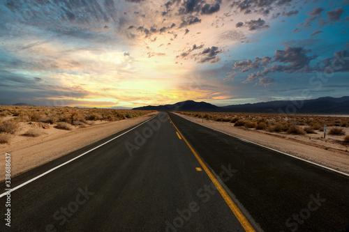 Autostrada nel deserto verso l'orizzonteal tramonto Canvas Print