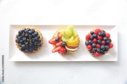Fototapeta High Angle View Of Fruit Tart On Plate Against White Background