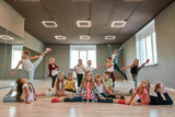 Keep dancing. Group of happy little boys and girls in fashionable clothes posing together in the dance studio. Dance team.