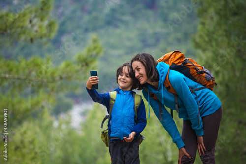 A child with a backpack takes a selfie on a smartphone with mom on the background of a mountain forest.