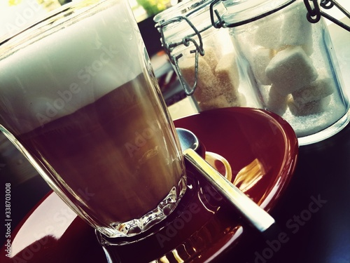 Canvas Tilt Image Of Coffee In Saucer With Spoon And Cookies Jar On Table